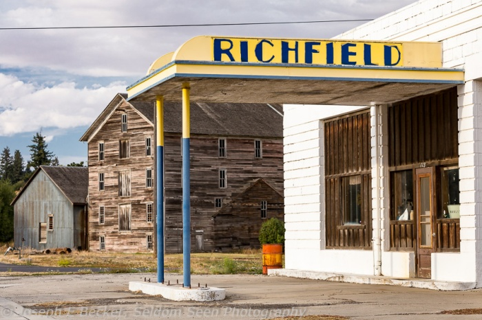 Old Richfield gas station with historic flour mill in the background in Oakesdale