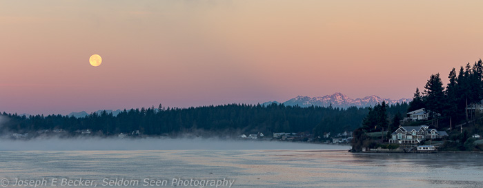 As the sun was rising, the moon was setting near the Olympic Mountains. This was taken just as the sun hit the mountains.